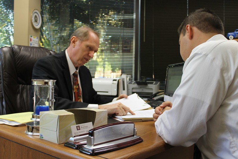man and attorney signing papers